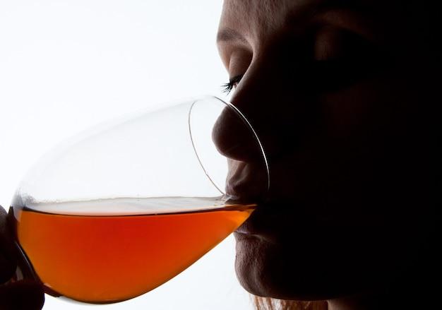 Silhueta de mulher degustando vinho