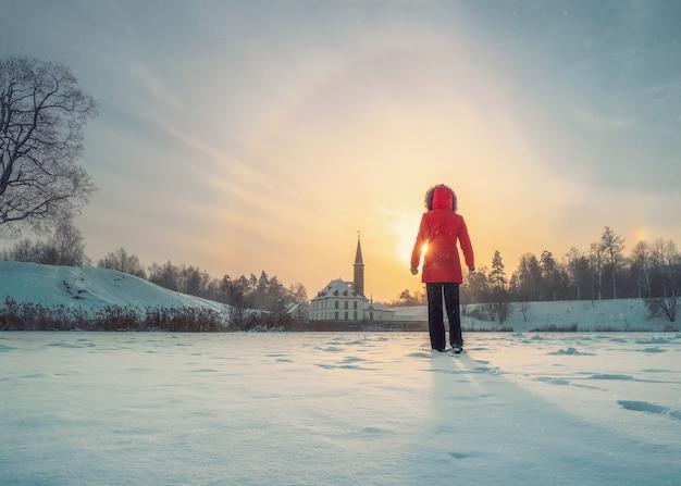 Silhueta de mulher em pé contra o céu ensolarado, perto do antigo castelo. temporada de inverno, raios de sol. foco suave.