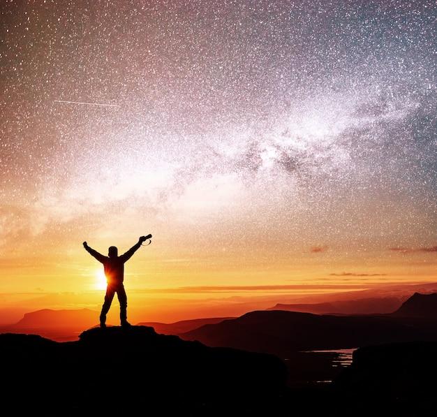 Silhueta de mulher está de pé no topo da montanha e apontando para a via láctea antes do nascer do sol e desfrutando com o céu noturno colorido