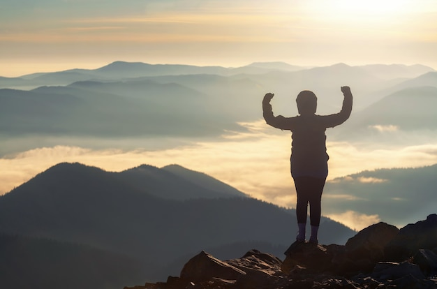 Silhueta de mulher forte no pico da montanha, flexionando os músculos, demonstrando autoconfiança e coragem.