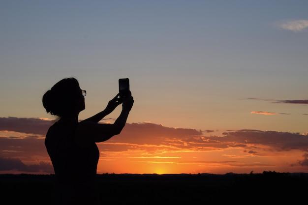 Silhueta de mulher fotografando o pôr do sol com o celular