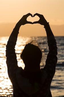 Silhueta de mulher jovem fazendo uma mão em forma de coração ao nascer do sol na praia.