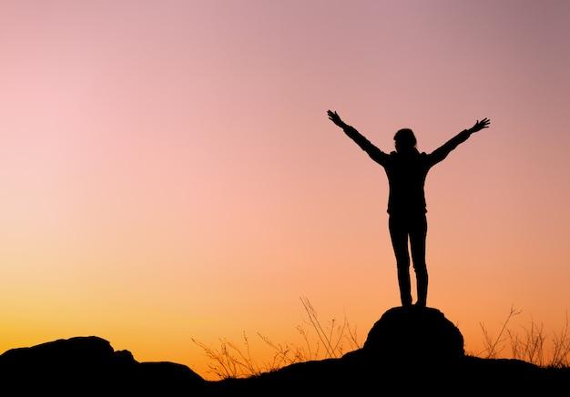 Silhueta de mulher jovem feliz contra lindo céu colorido