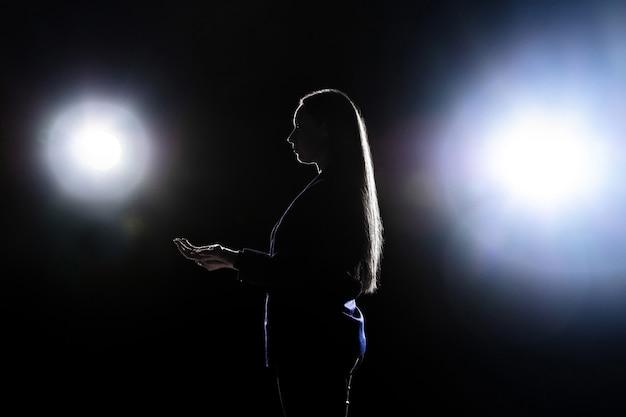 Silhueta de mulher jovem gesticulando isolada na parede preta com lanternas. copyspace.