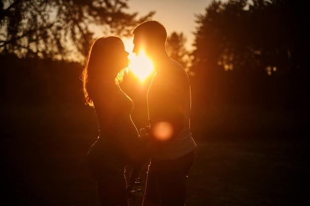 Silhueta de mulher jovem grávida e marido caminhando ao ar livre ao pôr do sol. família feliz, de mãos dadas na natureza na noite de verão. pais expectantes esperando o parto e curtir um ao outro em dia de sol