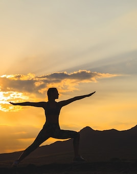 Silhueta de mulher jovem praticando ioga ou pilates no pôr do sol ou nascer do sol na localização da bela montanha.