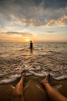 Silhueta de mulher na praia ao pôr do sol com pernas de homem.