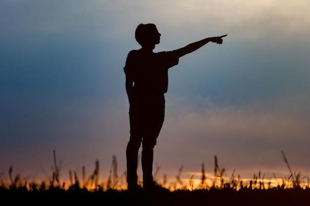 Silhueta de mulher posando ao pôr do sol