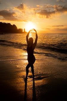 Silhueta de mulher posando na praia