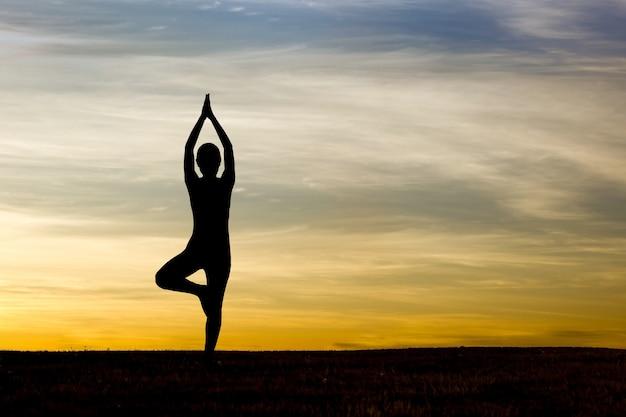 Silhueta de mulher praticando yoga no nascer do sol