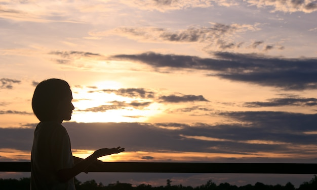 Silhueta de mulher que reza sobre o fundo bonito do por do sol.