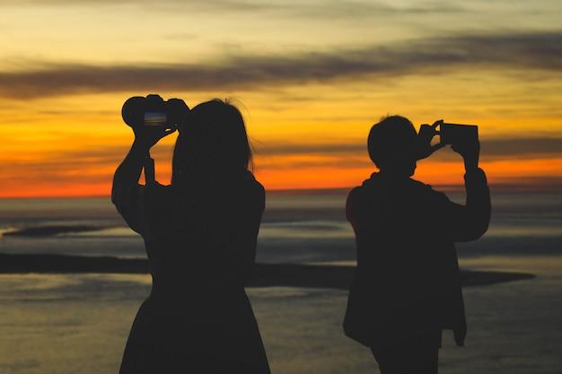 Silhueta de mulher segurando a câmera tirando fotos com a amiga durante o nascer ou o pôr do sol