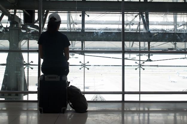 Silhueta de mulher sentada na mala de bagagem à espera de voo no aeroporto