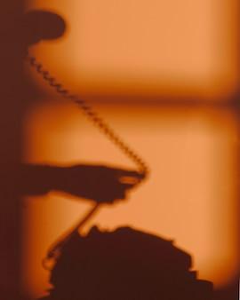 Silhueta de mulher usando um telefone
