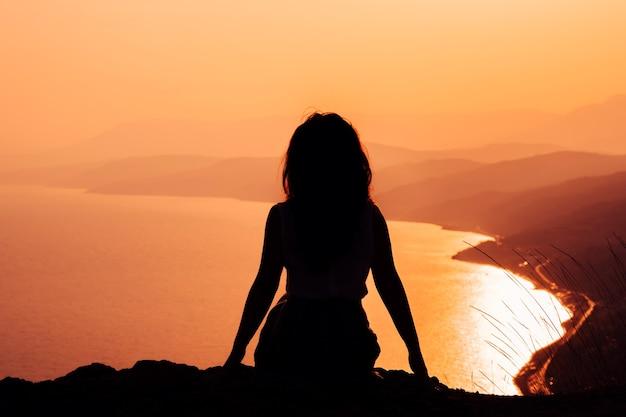 Silhueta de mulheres ao pôr do sol laranja em um penhasco com vista para as montanhas