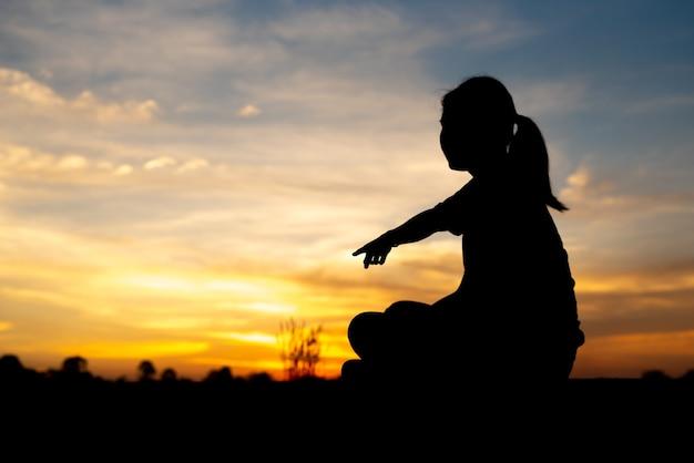 Silhueta de mulheres tristes e deprimidas, sentadas e apontando para a passarela do parque com o pôr do sol