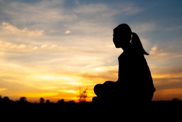 Silhueta de mulheres tristes e deprimidas sentadas na passarela do parque com o pôr do sol