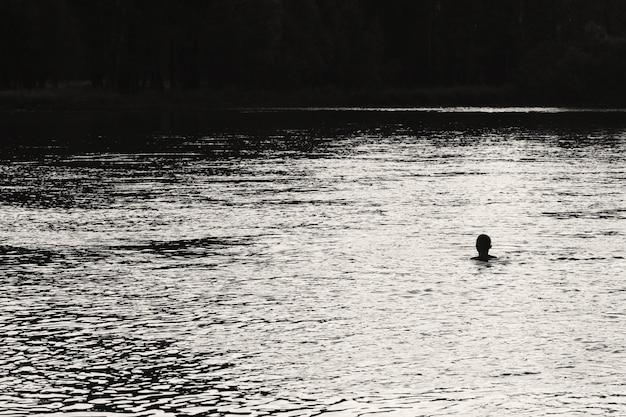 Silhueta de nadar homem no centro do rio no fundo da floresta. luz solar refletida na água em escala de cinza. água brilhante no rio. monocromática incrível paisagem atmosférica. cena minimalista.
