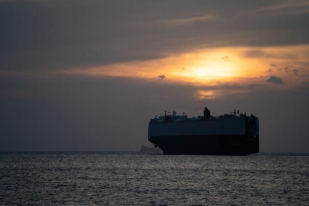 Silhueta de navio porta-contêineres de carga no mar durante o conceito do sol de logística e transporte