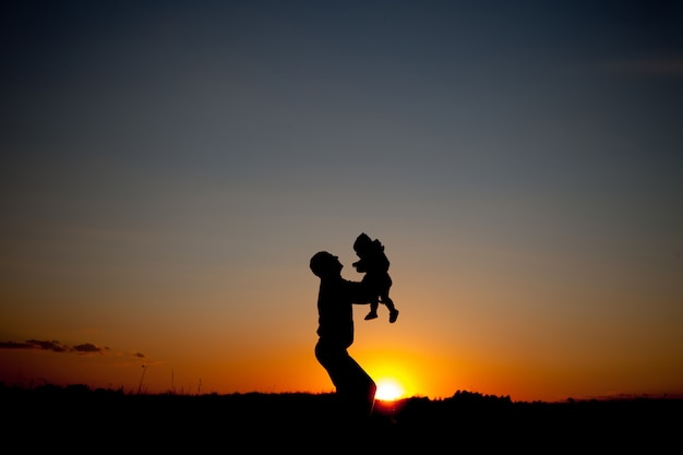 Silhueta de pai e filho no pôr do sol lindo de verão - família
