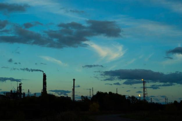 Silhueta de paisagem industrial com tochas industriais e colunas de fracionamento