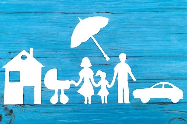 Silhueta de papel da família com carrinho de bebê sob o guarda-chuva