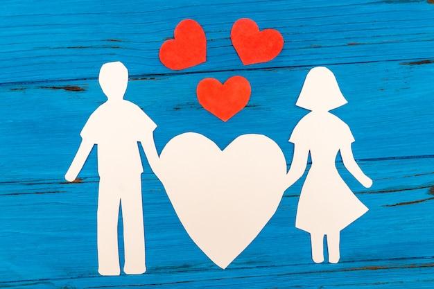 Silhueta de papel de homem e mulher segurando coração