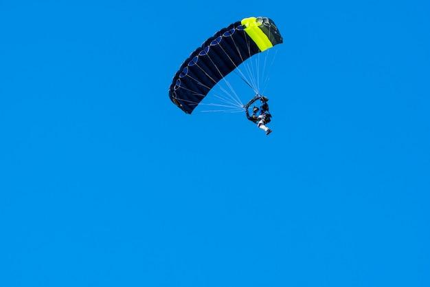 Silhueta de pára-quedista voando em céu azul claro