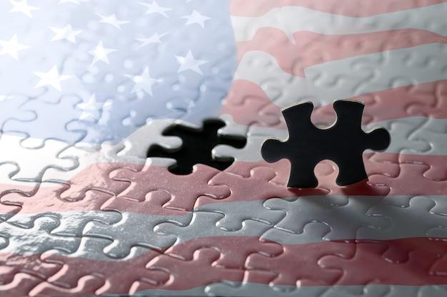 Silhueta de peça preta de quebra-cabeça. no fundo é uma bandeira dos estados unidos quebra-cabeça