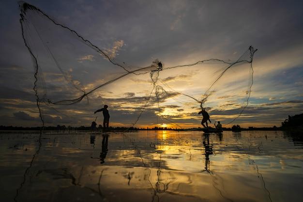 Silhueta de pescador no barco de pesca com rede no lago ao pôr do sol, tailândia