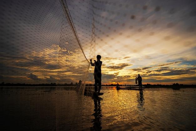 Silhueta de pescador no barco de pesca com rede no lago ao pôr do sol