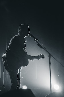 Silhueta de pessoa tocando violão à noite