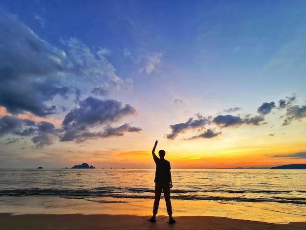 Silhueta de pessoas à noite na praia olhando o pôr do sol.