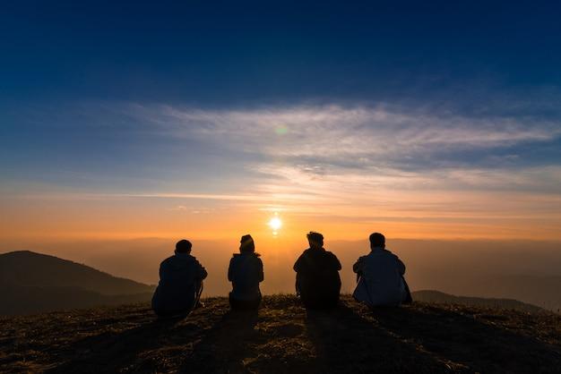 Silhueta de pessoas assistindo o pôr do sol