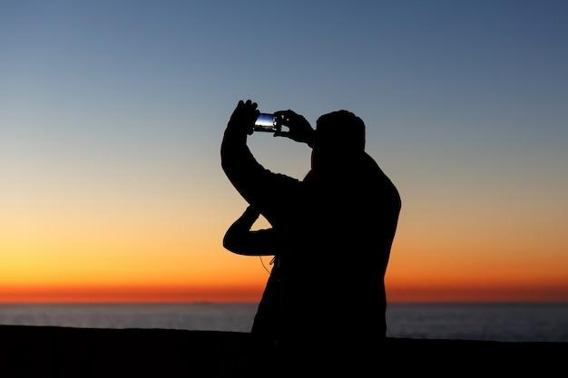 Silhueta de pessoas fotografando juntos lindo pôr do sol com smartphone
