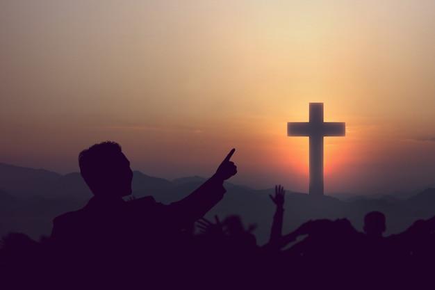 Silhueta de pessoas olhando para a cruz cristã com o fundo do céu ao nascer do sol
