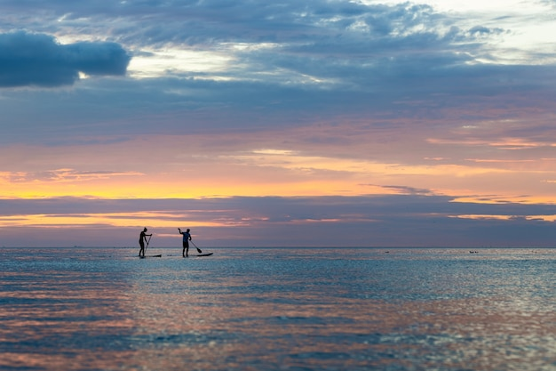 Silhueta de pessoas praticando paddleboard durante o pôr do sol