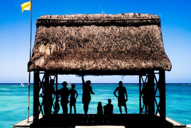 Silhueta de pessoas relaxando em uma casinha no cais do mar.
