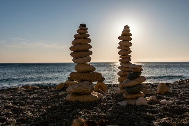 Silhueta de pirâmide de seixos balanceada na praia