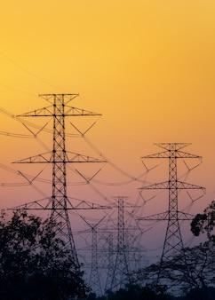 Silhueta de postes elétricos de alta tensão no céu pôr do sol