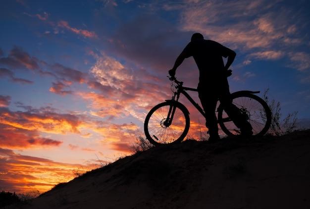 Silhueta de praticante de esportes, andar de bicicleta no prado, o belo pôr do sol. jovem andando de bicicleta.
