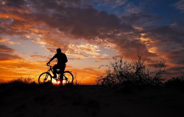 Silhueta de praticante de esportes, andar de bicicleta no prado, o belo pôr do sol.