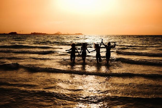 Silhueta de quatro meninas correndo no mar e de mãos dadas.