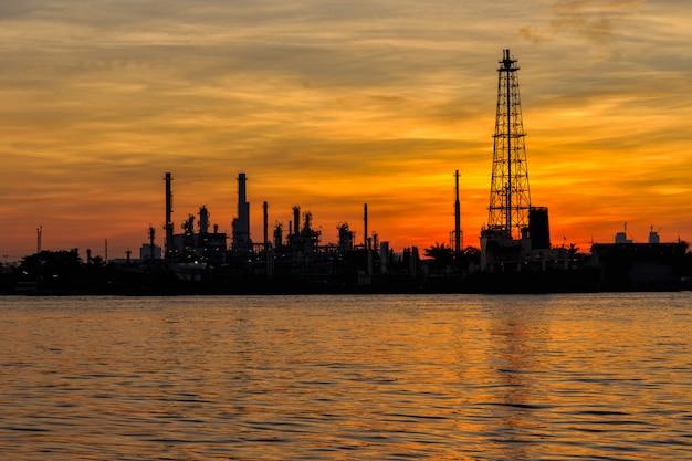 Silhueta de refinaria de petróleo ao longo do rio na hora do nascer do sol
