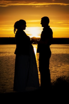 Silhueta de retrato vertical de homem com sua esposa grávida na praia ao pôr do sol amarelo