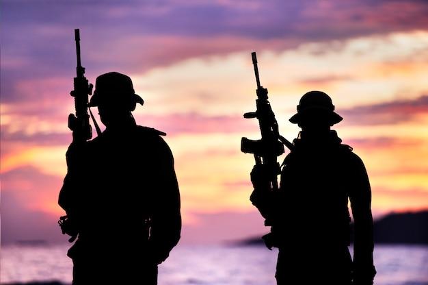 Silhueta de soldado carregando arma