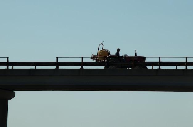 Silhueta de trator na ponte