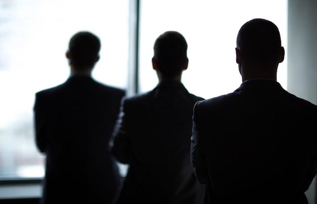 Silhueta de três empresários no escritório