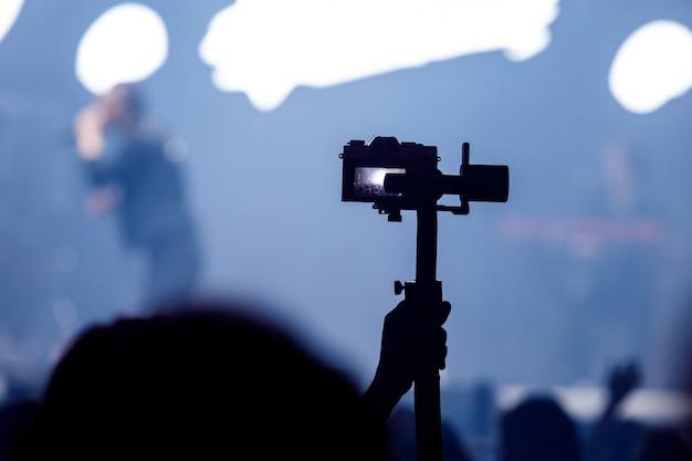 Silhueta de tripé com câmera no concerto.