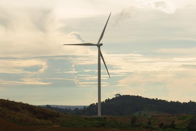 Silhueta de turbina de vento na montanha ao pôr do sol, energia renovável